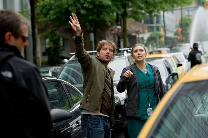 "Copyright: © 2014 WARNER BROS. ENTERTAINMENT INC. & LEGENDARY PICTURES PRODUCTIONS LLC  Photo Credit: Kimberley French  Caption: (L-r) Director GARETH EDWARDS and ELIZABETH OLSEN on the set of Warner Bros. Pictures' and Legendary Pictures' epic action adventure ""GODZILLA,"" a Warner Bros. Pictures release."