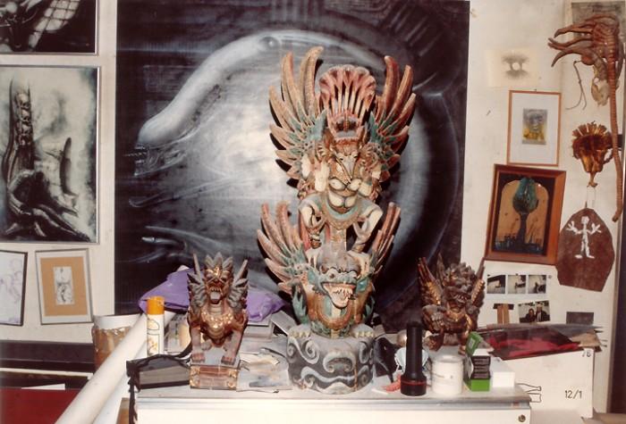 Holzgeschnitzte Dämonenfiguren, Totems, Fetische und mit Bildern überfrachtete Wände dominieren in der gesamten Behausung. Rechts ein Originalmodell des Face-Huggers aus Alien I.